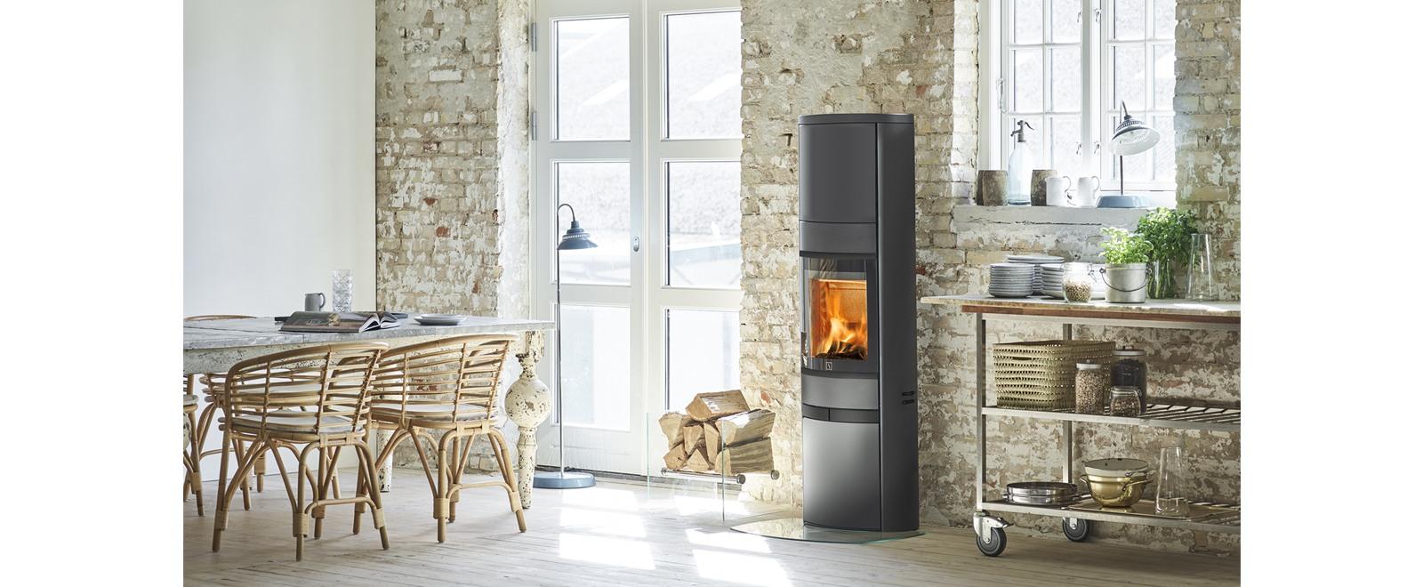 Scan 68 i stål i sort lakk med høy topp og sorte lister med plass til varmelagring i toppen. Peisovn står elegant i et moderne dansk kjøkken.