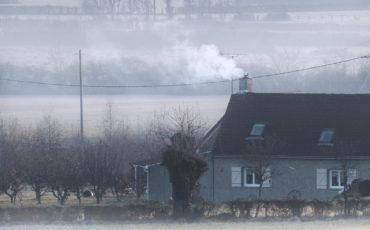 Kaldt hus på jorde med røyk fra pipe og frostrøyk på bakken