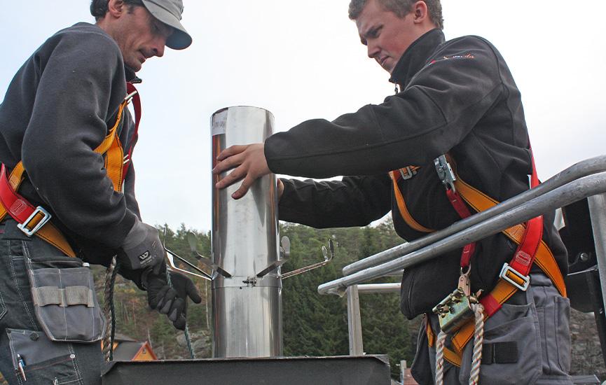 To menn monterer stålpipe på taket