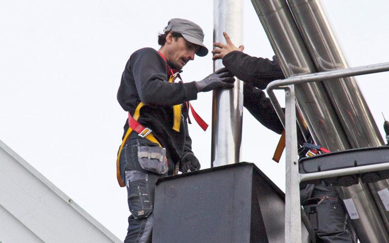 To menn som gjør piperehabilitering med stålpipe på taket